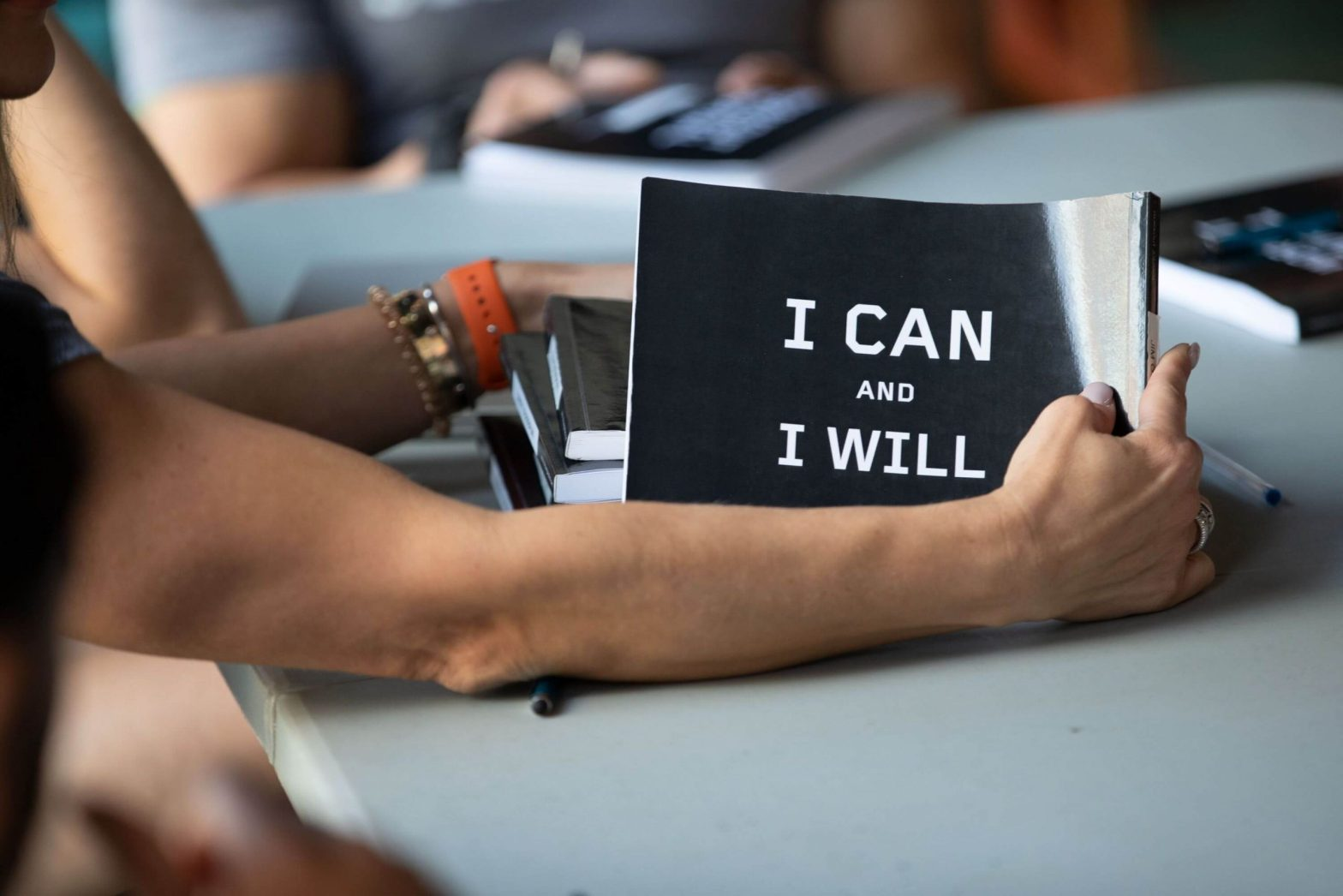 """A hand holding a board that says """"I can I will"""". This is a motivation quote to state that exercise order can build your workout."""
