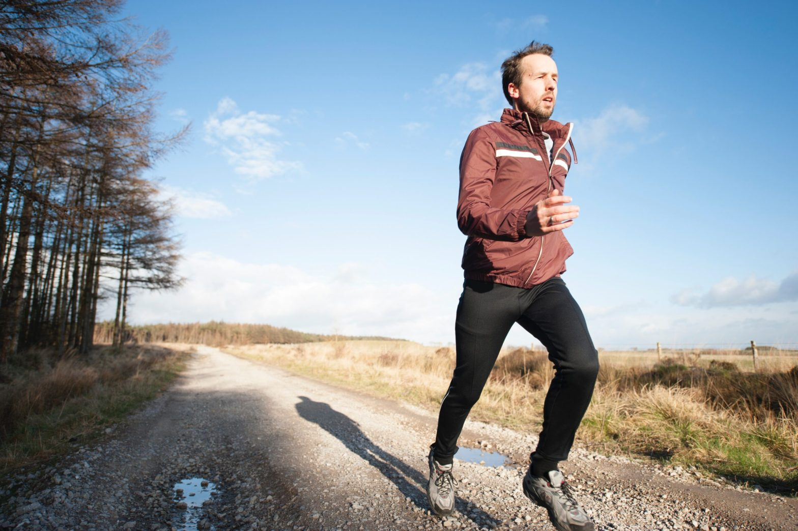 Man running on a field, the sky is behind him. Fitness benefits.