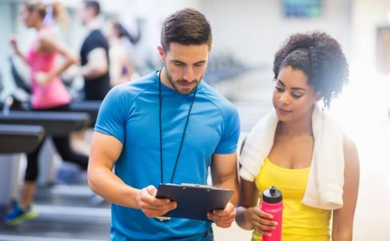 trainer with his client. is your trainer hindering your fitness goals?