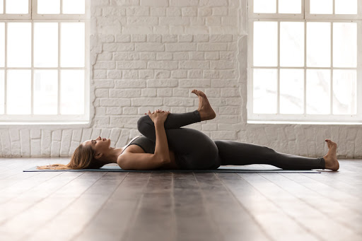 Woman stretching her legs on the floor, this is the difference between mobility and stretching.