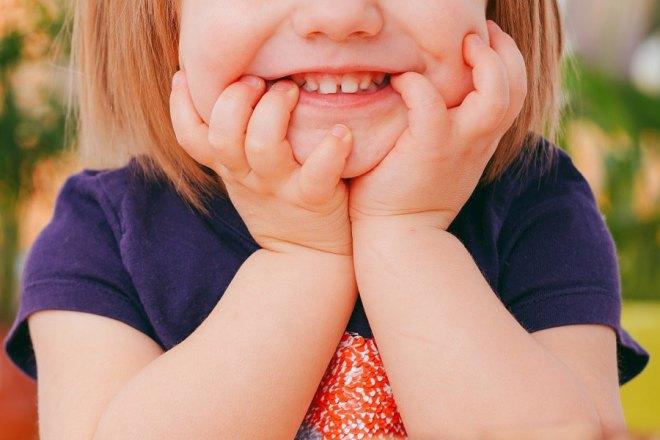 Una niña enseña sus dientes.