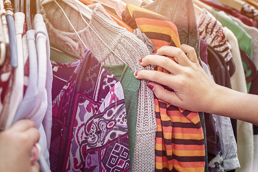 A hand browsing through some clothing