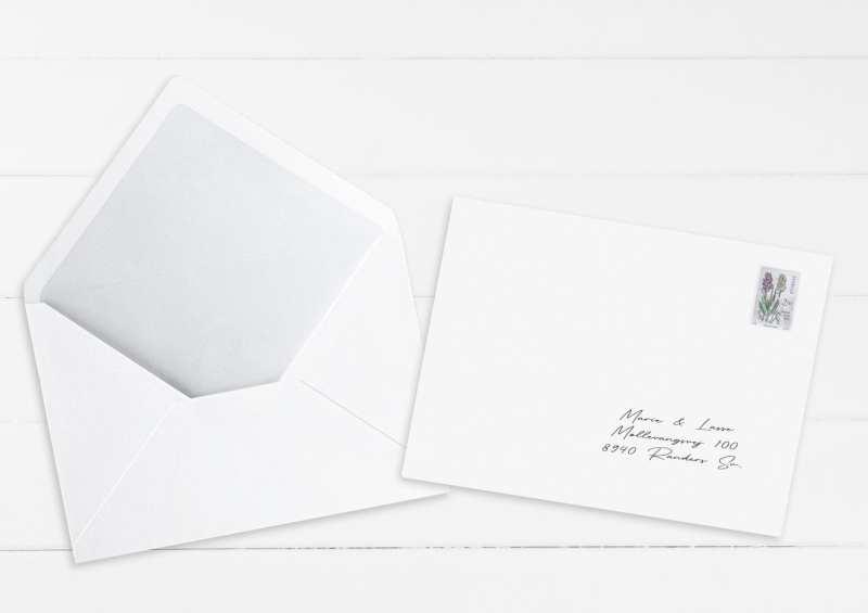 Hvide kuverter med indsatte navne og adresser på gæsterne