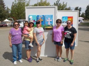 "By J. M. Swezey Art of Life artist Giselda Martin (third from right) stands next to her painting ""Stronger."" She is flanked (left to right) by her mom, Amparo, niece Amelia and sisters Irma, Mary and Elva"