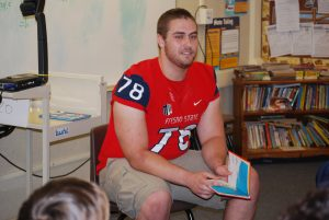 """Photo by Valerie Shelton Football player David Patterson, a junior at Fresno State majoring in Computer Science, reads """"Green Eggs and Ham"""" to students in Mrs. Martinez' sixth grade class."""