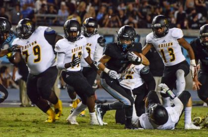 Running back Jordan Ayerza of Clovis North tries to break away from the pack in the Broncos victory over Edison to move the team to 3-1 on the season. Ayerza rushed for 84 yards in the game. [Photo by Nick Baker]