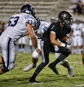 Clovis North running back No. 1 Jordan Ayerza escapes two Bellarmine defensive players. Ayerza scored on a 3-yard touchdown run in the second quarter. [Photo by DeAnna Turner]