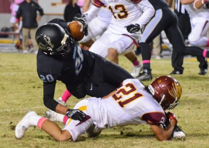Photo by Nick Baker - Clovis North wide receiver Chad Fugman is upended by Clovis West defensive back Dakota Helms. Fugman earlier scored on a 62-yard pass from Brent Bailey to give the Broncos a 6-0 lead early.