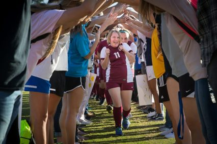 Melisse Poole of Clovis West runs through a human tunnel made up of the student body, coaches and family members after their game against Clovis. [Photo by Ron Webb]