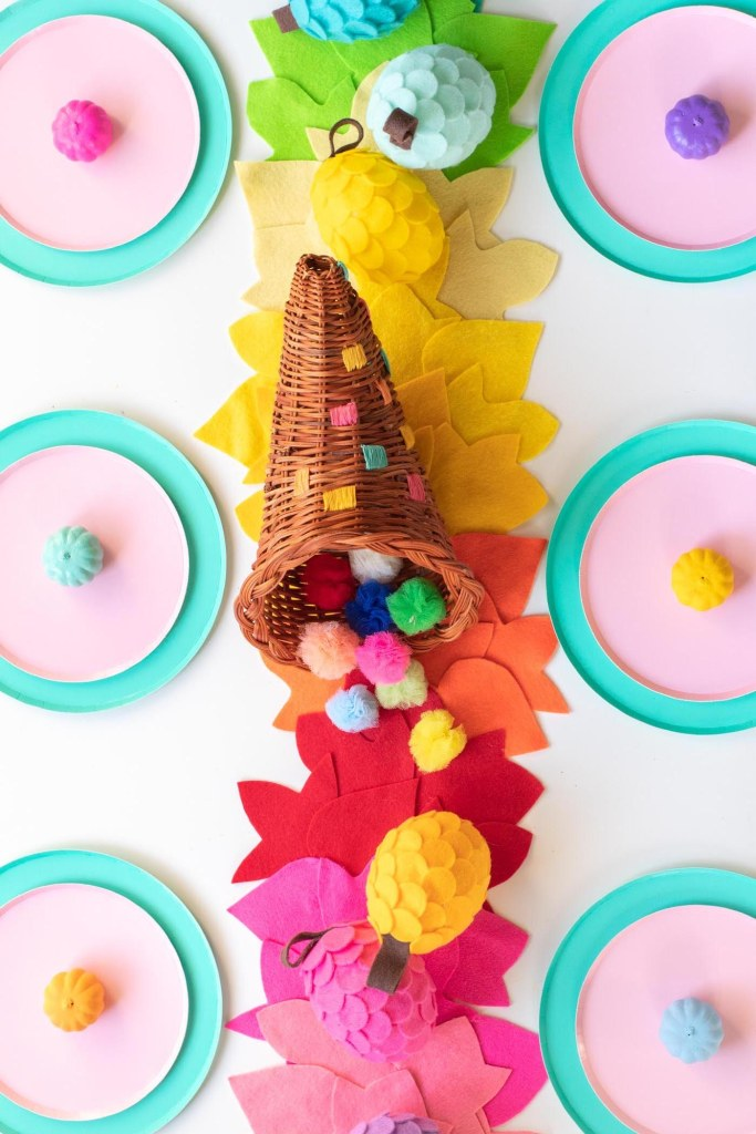 DIY No-Sew Rainbow Leaf Table Runner // Decorate for fall or Thanksgiving with a colorful no-sew table runner made from felt! Cut different leaf shapes to make a rainbow table runner for your dinner table or entryway! #rainbow #diy #entertaining #tablerunner #thanksgiving #thanksgivingdiy #feltcrafts #nosew #rainbowparty #rainbowdecor