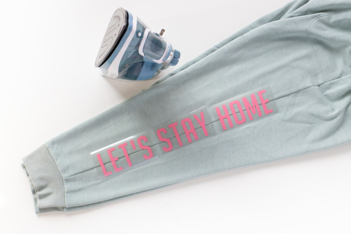 """""""Let's Stay Home"""" DIY Graphic Sweatpants with Iron-On Vinyl (Cricut) // Update a pair of plain sweats with a cute saying using vinyl! #cricutmade #ironon #vinyl #fashion #diyfashion #nosew #sweatpants #womensstyle #stylediy"""