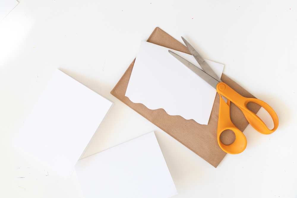 cutting white roofs for paper gingerbread house gift bags