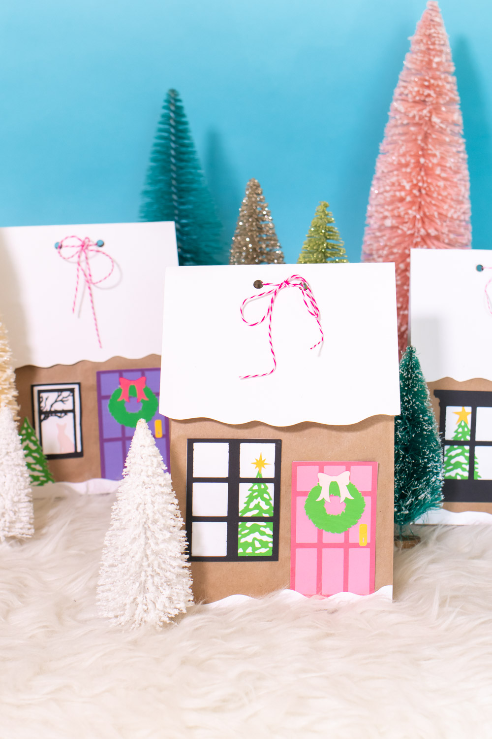 assortment of gingerbread house paper gift bags surrounded by bottlebrush trees