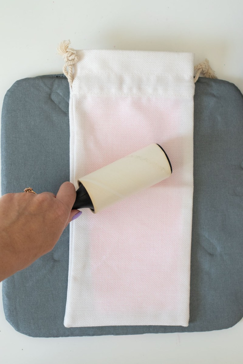hand rolling away lint from DIY wine bag packaging