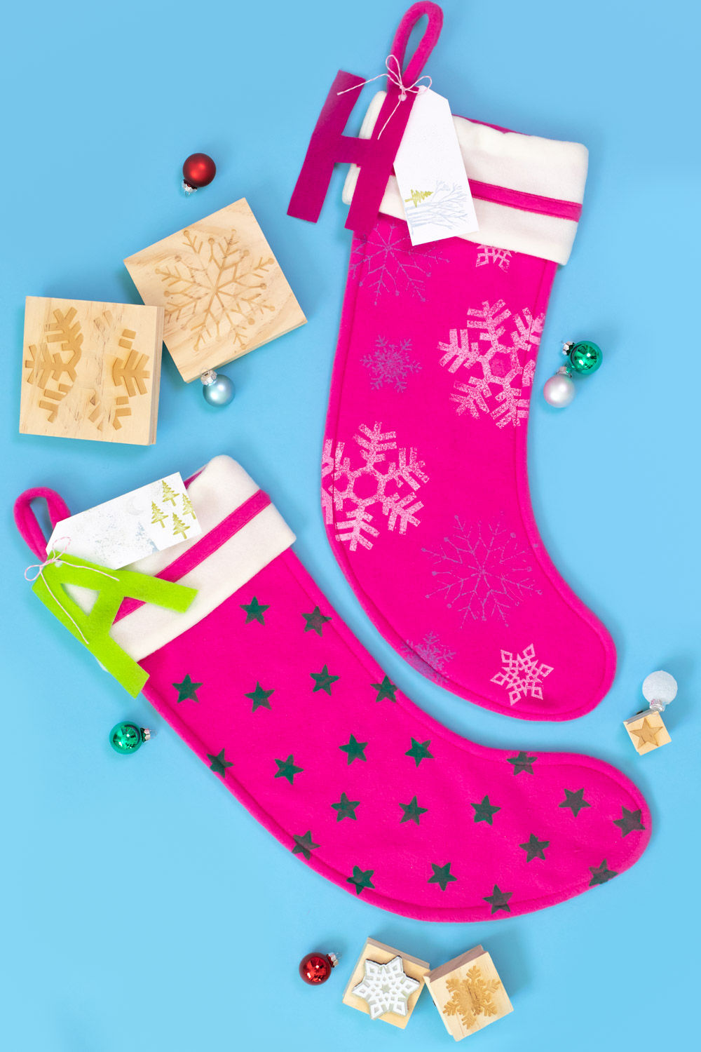 two stamped stockings lay flat with ornaments and stamps