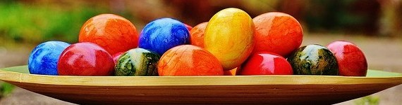 A plate with brightly colored Easter eggs piled on it