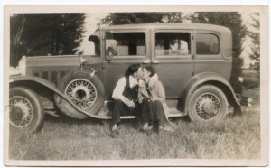 Bonnie and Clyde pictured sitting on the running board of an old Ford.