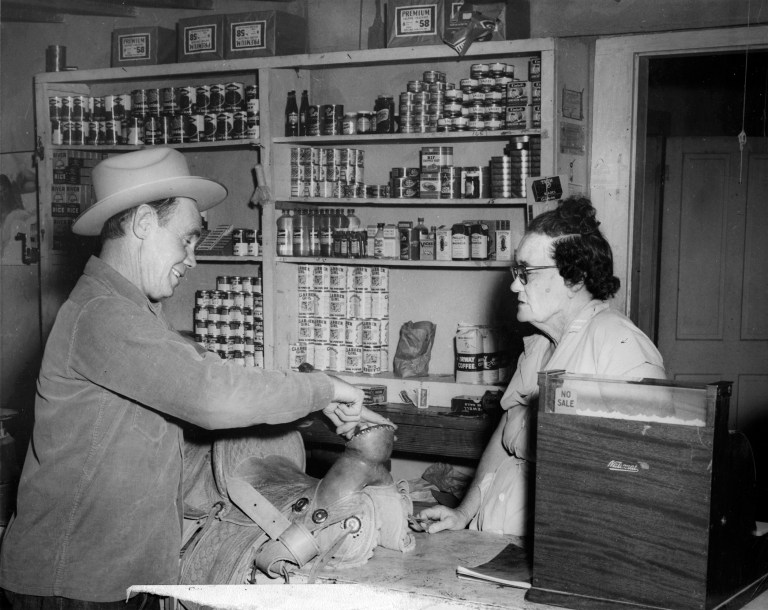 B&W photo of Maggie behind a small sales counter selling a saddle to a customer. Photo by Glenn Burgess, courtesy of the Archive of the Big Bend.