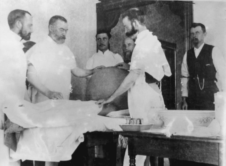Dr. Spohn, wearing scrubs, prepares to operate on the famous 328 pound tumor.