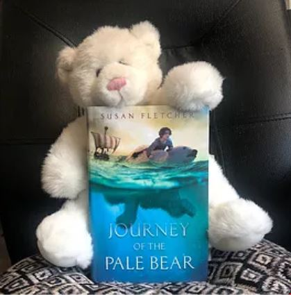 Bookstagram by Kelly: hardcover edition of Journey of the Pale Bear being held by a white teddy bear.