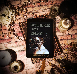 Bookstragram by Taylor: photo showing cover of Violence / Joy / Chaos on brick-textured surface, surrounded by scented candles, blooming white roses and beads