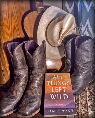 Bookstagram: photo of book sitting among cowboy boots and a straw cowboy hat and a guitar.