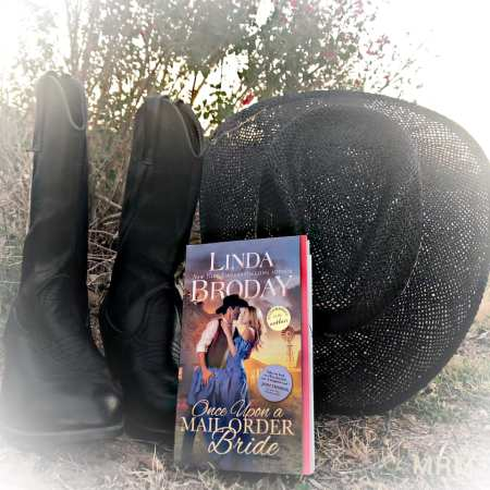 Bookstagram: paperback book leaning against black cowboy hat and black western boots.