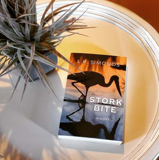 Bookstagram: Photo of Stork Bite paperback sitting on white, circular table, with a small potted plant nearby.