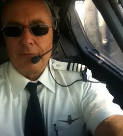 Image of Chris Manno wearing his airline captain uniform, sitting in the cockpit, wearing sunglasses and a microphone headset.