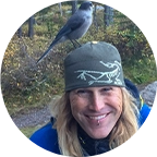 Andrea Keeler with whiskey jack bird sitting on head