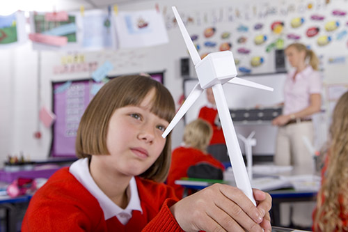 Serious school girl looking at model wind turbine in classroom