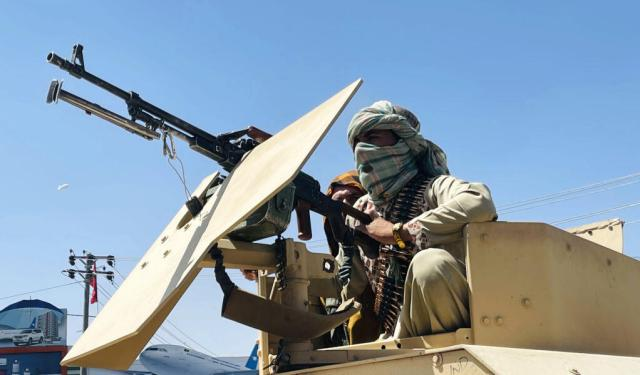 Taliban fighter with a vehicle-mounted machine gun