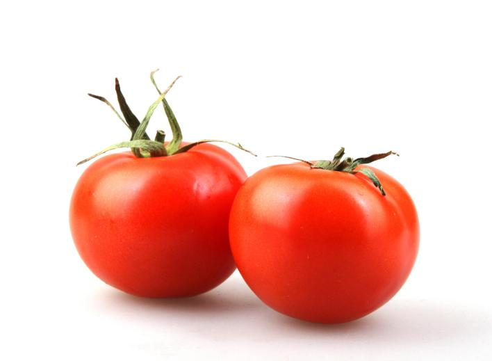 two ripe tomatoes on a white background