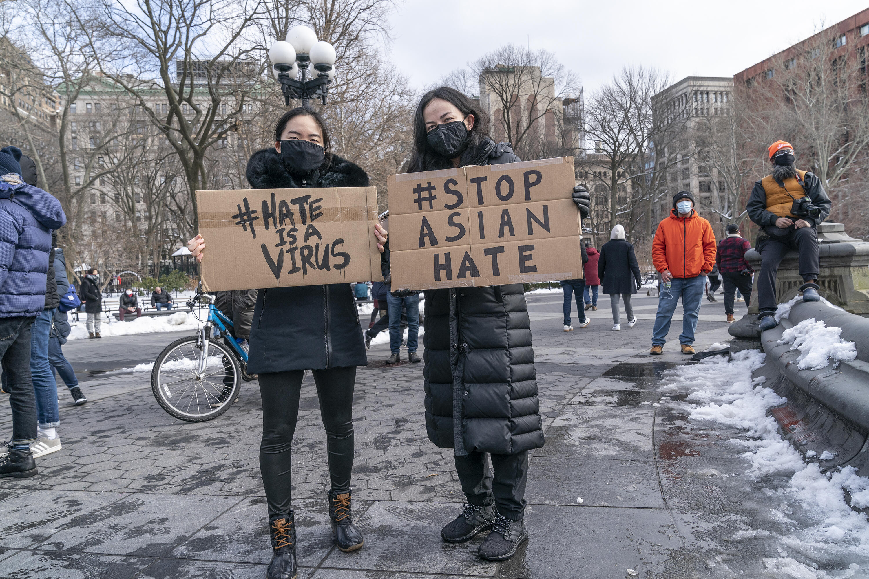 """Two women holding signs saying """"#Hate is a virus"""" and """"#Stop Asian hate"""""""