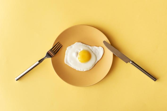 fried egg on a yellow plate on yellow background