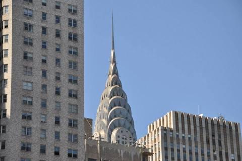 Apparition furtive de la flèche du Chrysler building au-dessus d'un buildin