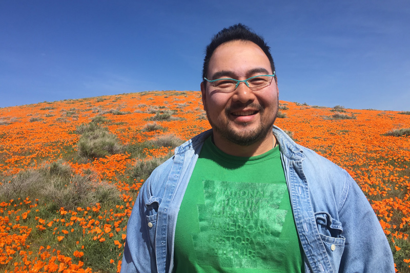 Richard smiles with a hill filled with orange CA poppies behind him. He's wearing a green tshirt, denim shirt, and glasses.