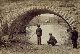 two men under bridge near water