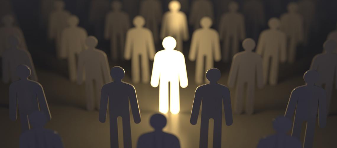 La silueta de papel de un hombre está iluminada en el centro de otras siluetas apagadas para simbolizar la esencia del liderazgo