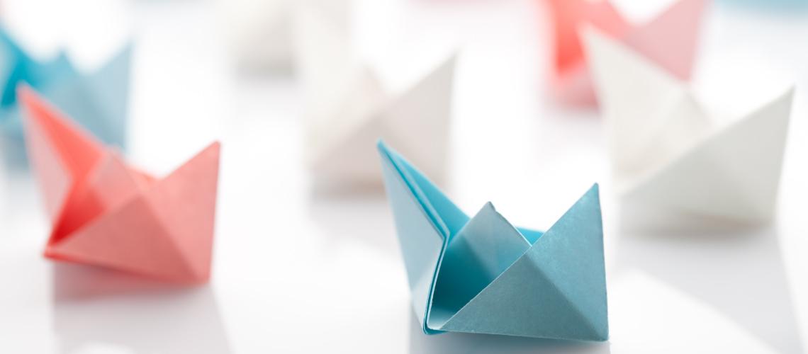 Unos barcos de papel en colores pasteles están agrupados de tal forma que se puede observar un líder para representar la etimología de liderazgo