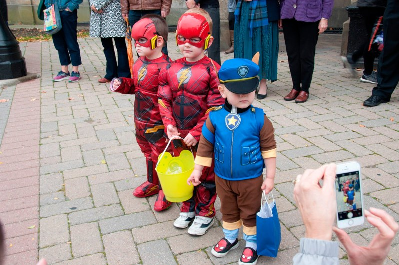 Three kids dressed for Halloween joining in the celebration