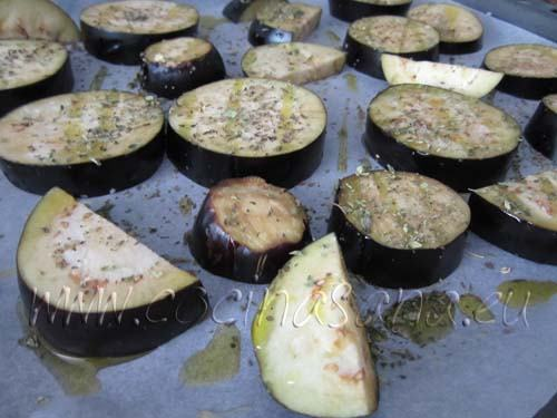 Luego pon las lonchas en una bandeja forrada con papel horno y hornea las berenjenas hasta que estén doraditas