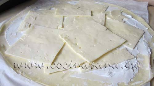 a continuación coloca las lonchas de queso cubriendo la superficie de toda la masa.