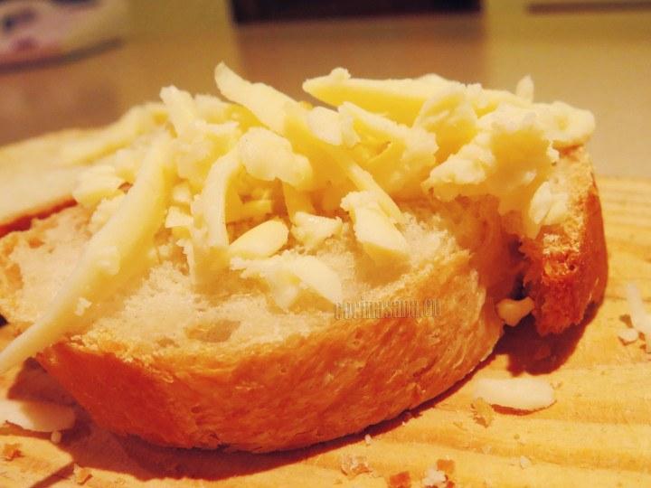 Cortar el pan agregar la mantequilla y el queso rallado