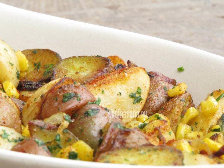 Ensalada de papa finalizada. Se pueden ver las papas o patatas con el maíz amarillo, el cilantro y el pimentón o paprika