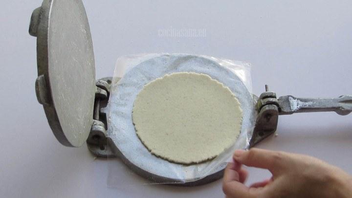 Retirar las tortillas de maíz de la prensa con cuidado para colocarlas en la sarten
