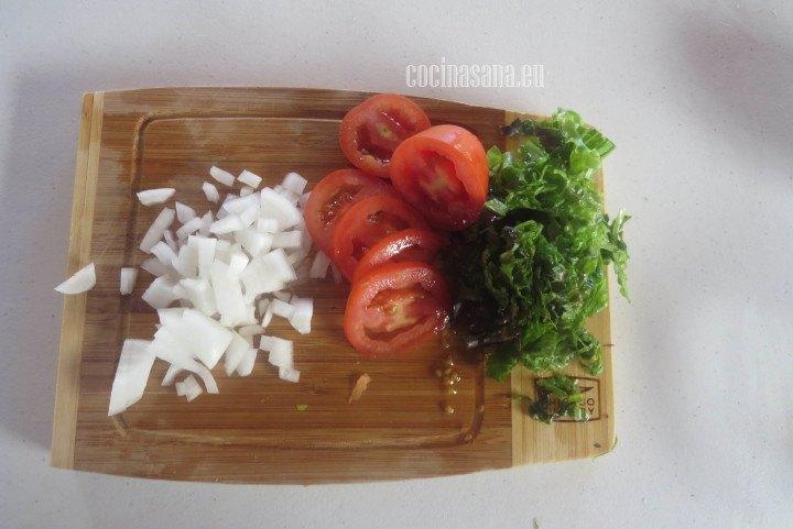 Picar las verduras para acompañar el pollo, rebana el tomate, pica la cebolla y rebana la lechuga