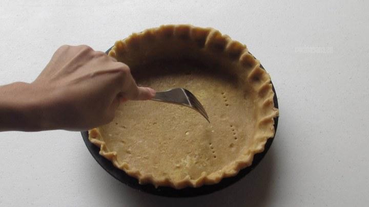 pinchar la masa con un tenedor par evitar que se levante durante la cocción.  También es bueno colocar un poco de frijoles secos como contrapeso.