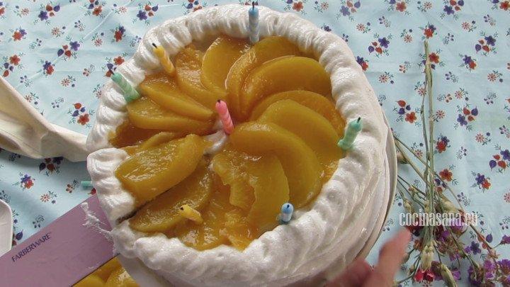Pastel de 3 leches terminado, decorado con velas de cumpleaños, merengue italiano y también duraznos en almíbar.