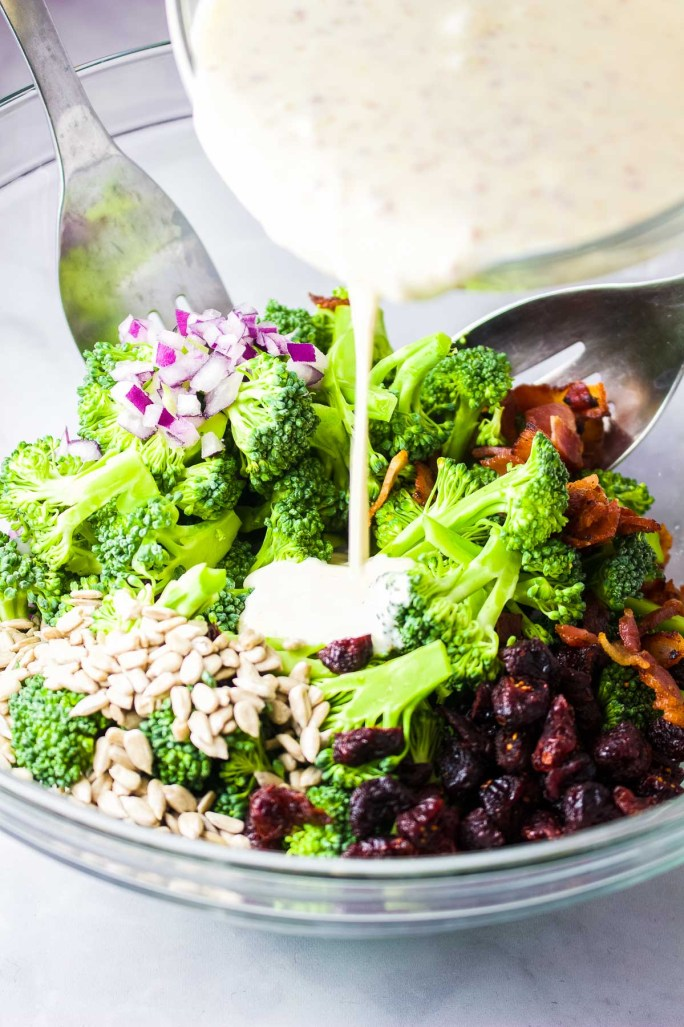 broccoli salad with dressing pour. creamy dressing